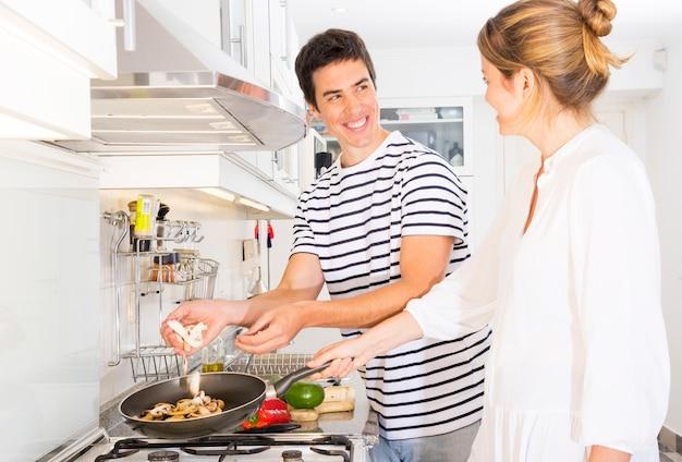 Pareja feliz de pie en la cocina preparando setas en sartén
