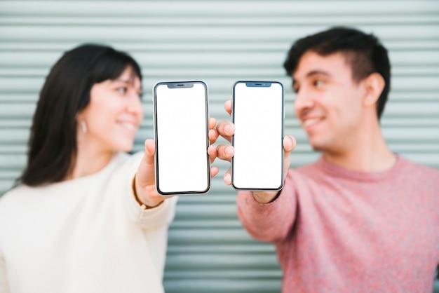 Pareja feliz de pie con teléfonos inteligentes