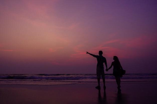 Pareja feliz en la playa disfrutando de la puesta de sol