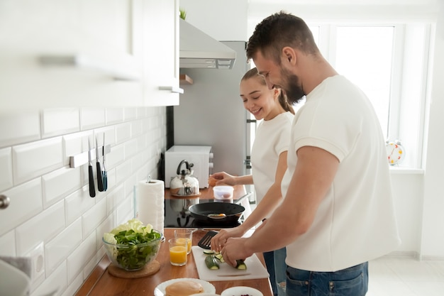 Pareja feliz preparando el desayuno juntos en la cocina en la mañana