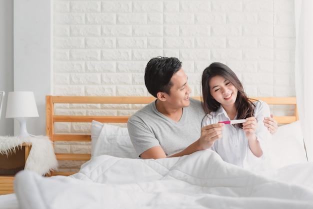 Pareja feliz con prueba de embarazo en dormitorio