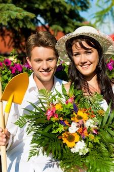Pareja feliz con ramo de flores y herramientas de jardinería posando en el jardín