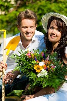 Pareja feliz con ramo de flores y herramientas de jardinería