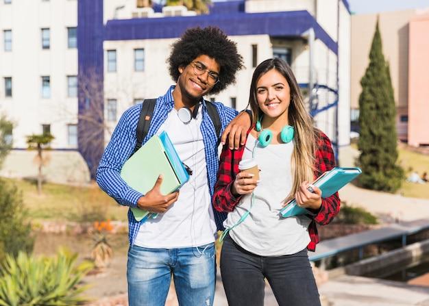 Pareja feliz de raza mixta posando delante del edificio de la universidad
