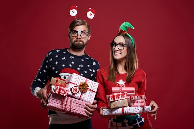 Pareja feliz con regalos sobre fondo rojo.