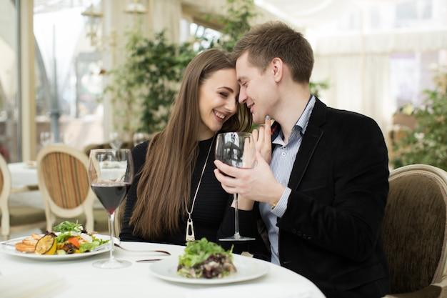 Pareja feliz en el restaurante, disfrutando del vino y la ensalada.