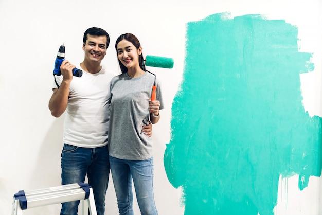 Pareja feliz con rodillo de pintura y pintura de pared
