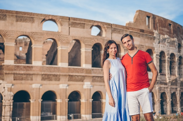 Pareja feliz en roma sobre fondo coliseo. vacaciones italianas europeas