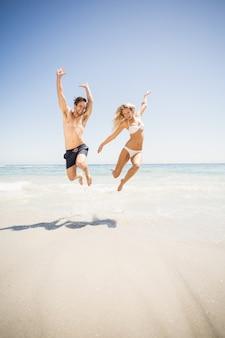Pareja feliz saltando en la playa