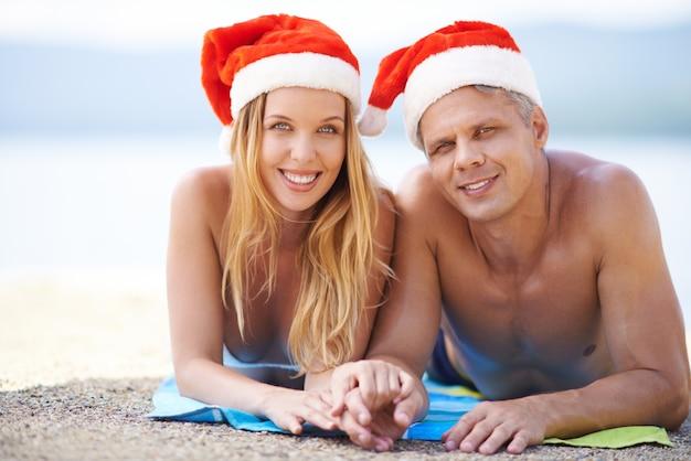 Pareja feliz con sombrero de santa en la playa