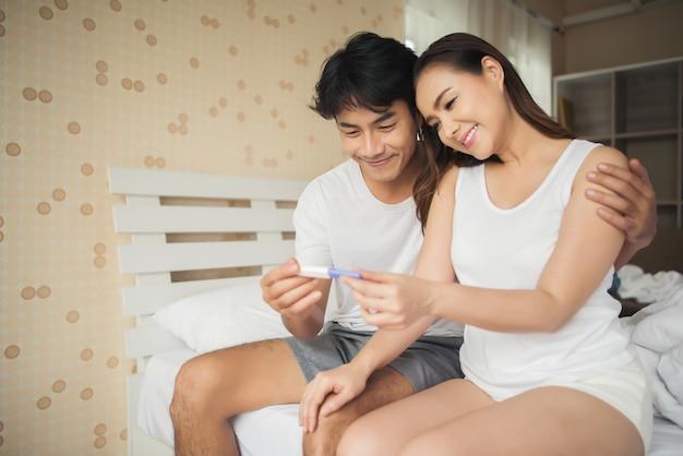 Pareja feliz sonriendo después de descubrir prueba de embarazo positiva en el dormitorio