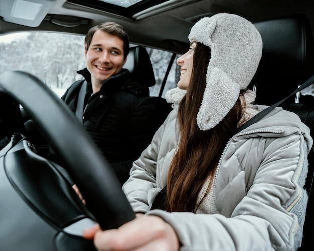 Pareja feliz y sonriente juntos en el coche durante un viaje por carretera