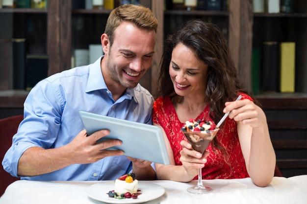 Pareja feliz con tableta digital mientras tiene desierto