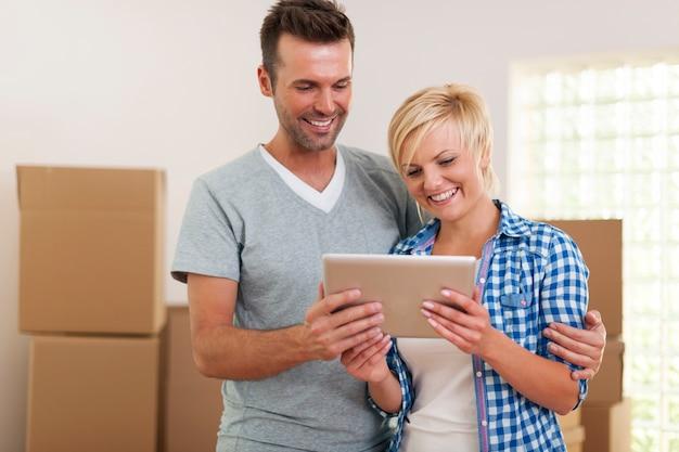 Pareja feliz con tableta digital durante la mudanza