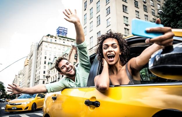Pareja feliz en un taxi amarillo en nueva york