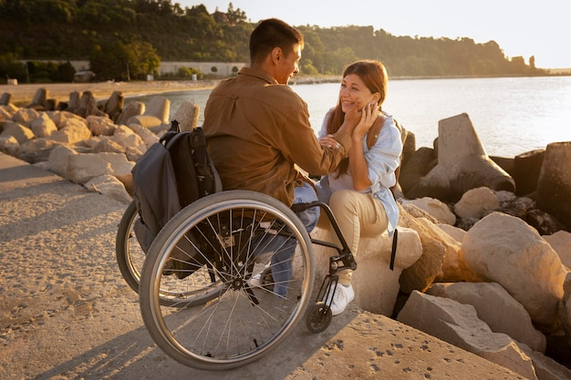 Pareja feliz de tiro completo con silla de ruedas