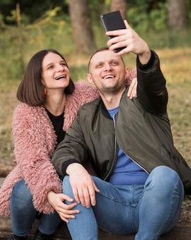 Pareja feliz de tiro medio tomando selfie
