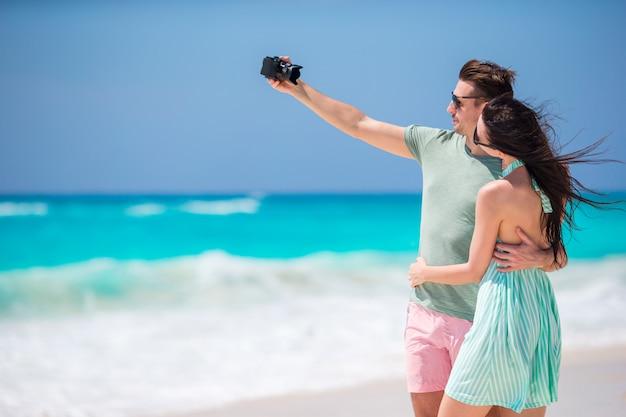 Pareja feliz tomando una foto en una playa en vacaciones