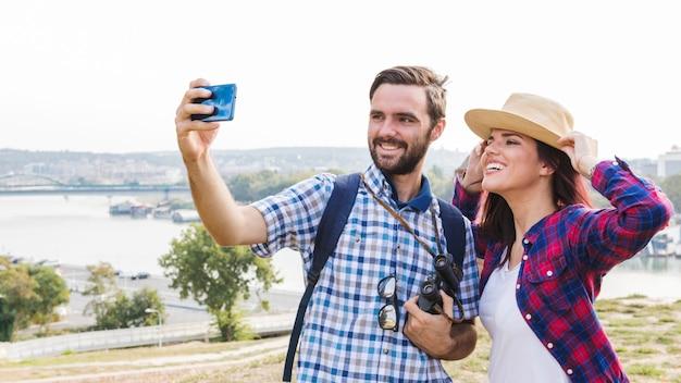 Pareja feliz tomando selfie en teléfono inteligente al aire libre