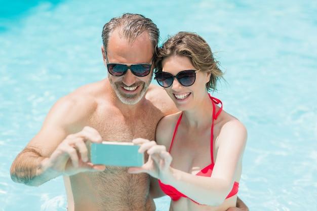 Pareja feliz tomando selfie desde teléfono móvil en la piscina