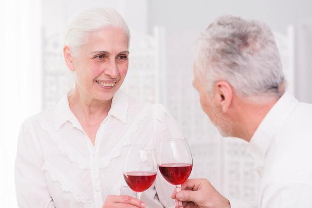 Pareja feliz tostado copas de vino juntos en casa
