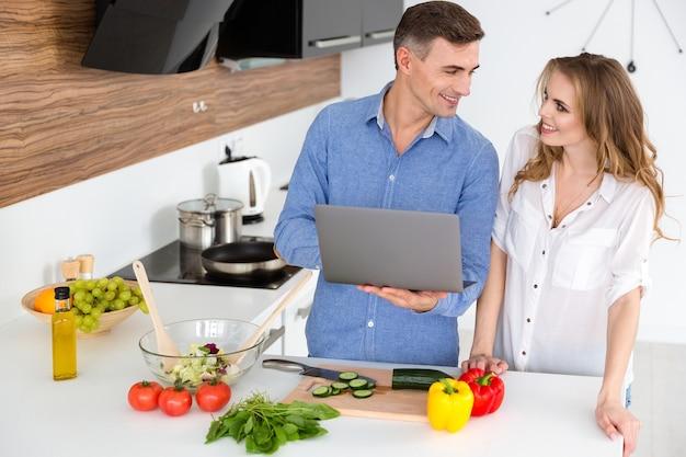 Pareja feliz usando laptop y preparando platos vegetarianos en la cocina de casa