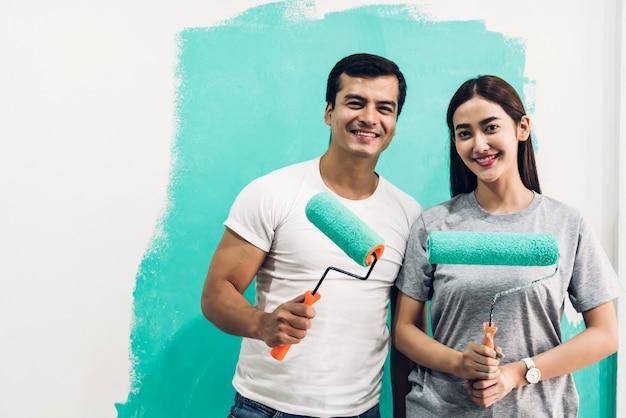 Pareja feliz usando un rodillo de pintura y pintando paredes en su nuevo hogar