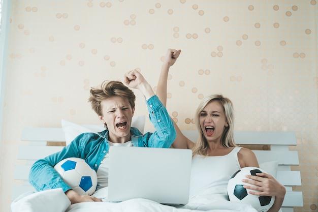 Pareja feliz viendo fútbol soccer en la cama
