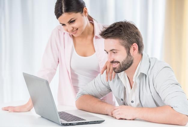 Pareja feliz viendo películas en la computadora portátil.