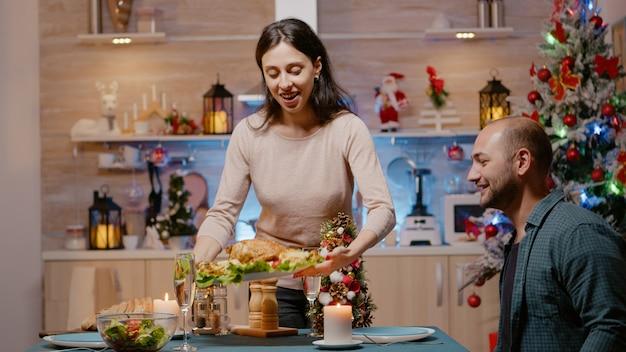 Pareja festiva preparándose para la cena de nochebuena en casa