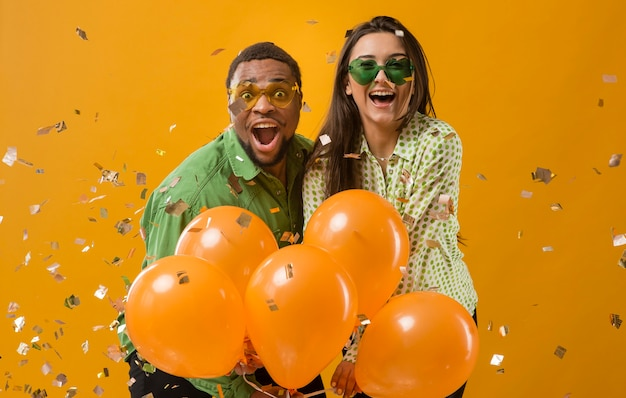 Pareja en fiesta divirtiéndose y sosteniendo globos