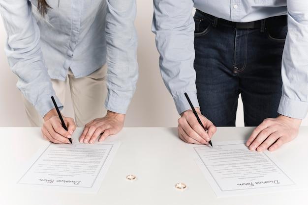 Pareja firmando formularios de divorcio juntos