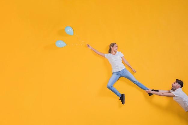 Pareja flotando en el aire con globos