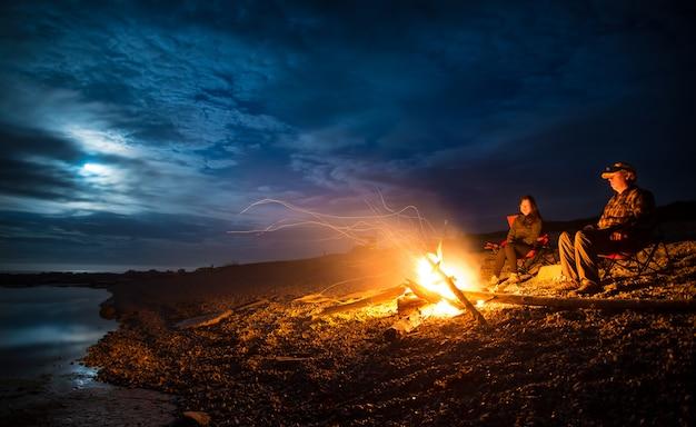 Pareja con fogata en la playa rocosa en la noche