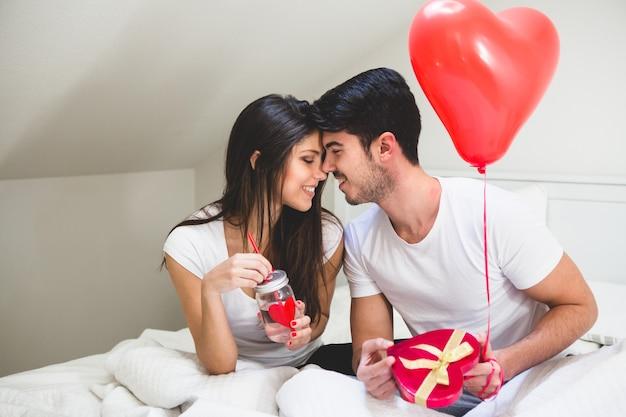 Pareja frente con frente mientras el novio sujeta un regalo y un globo