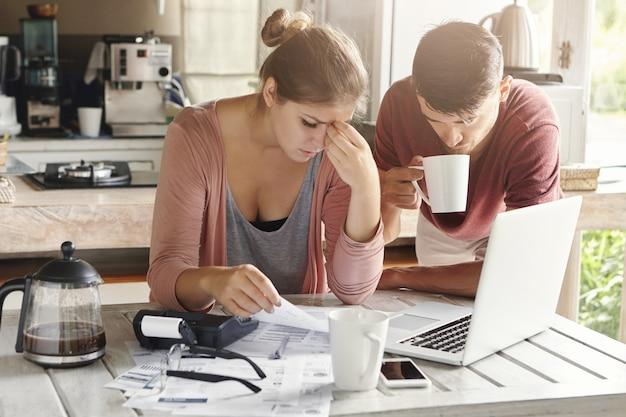 Pareja frente a un problema financiero, no pagar el préstamo en el banco. mujer estresada manejando el presupuesto familiar, haciendo cálculos usando una computadora portátil y una calculadora, su esposo parado junto a ella con una taza de té