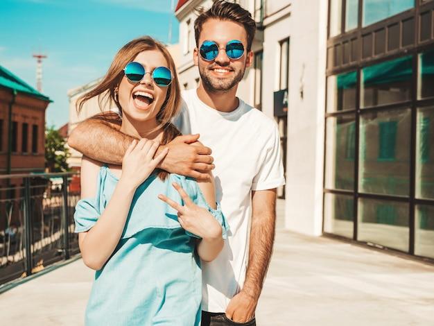 Pareja con gafas de sol posando en la calle