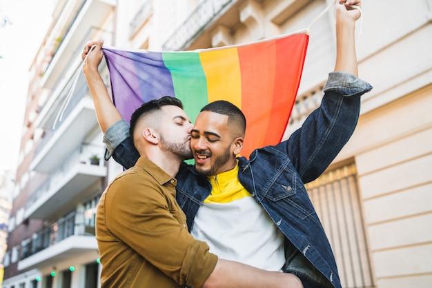 Pareja gay abrazando y mostrando su amor con la bandera del arco iris.