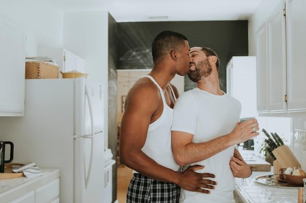 Pareja gay abrazándose en la cocina