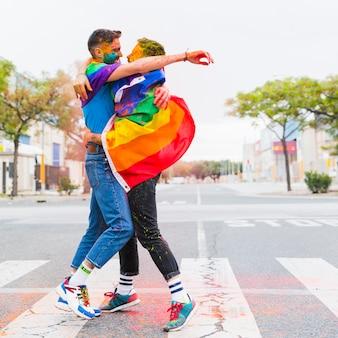 Pareja gay alegre abrazando envuelto en banderas de arco iris en el camino