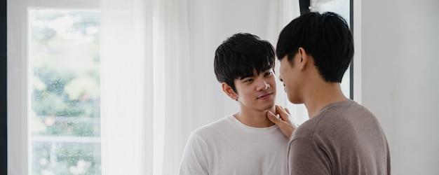 Pareja gay asiática de pie y abrazando cerca de la ventana en casa. jóvenes asiáticos lgbtq + hombres besándose felices relajarse descansar juntos pasar tiempo romántico en la sala de estar en casa moderna en la mañana.