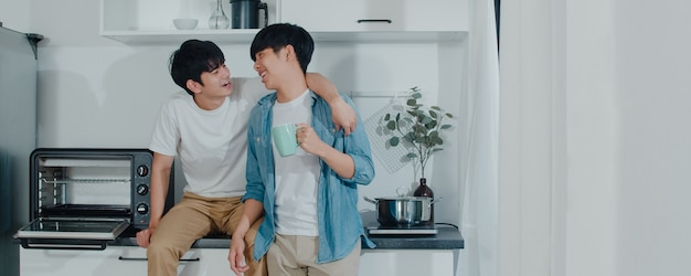 Pareja gay asiática tomando café, pasando un buen rato en casa. los jóvenes y guapos hombres lgbtq + que hablan felices se relajan descansan juntos y pasan un momento romántico en la moderna cocina de la casa por la mañana.