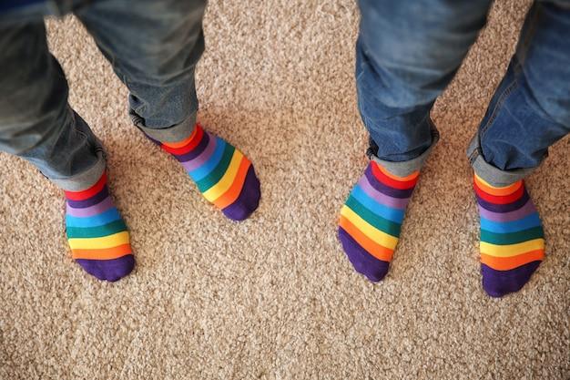 Una pareja gay con coloridos calcetines de pie sobre una alfombra, vista superior