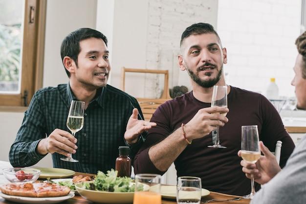 Pareja gay interracial que tiene fiesta bebiendo y comiendo en casa