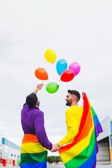 Pareja gay lanzando globos de arcoiris en el cielo