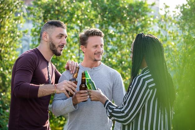 Pareja gay y mujer afroamericana amiga disfrutando de beber alcohol