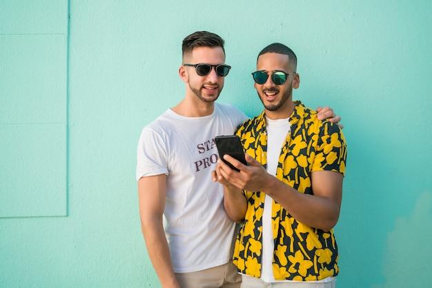 Pareja gay pasar tiempo juntos mientras usa el teléfono.