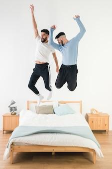 Pareja gay saltando en la cama en el dormitorio