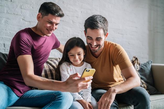 Una pareja gay y su hija usando un teléfono móvil en casa.