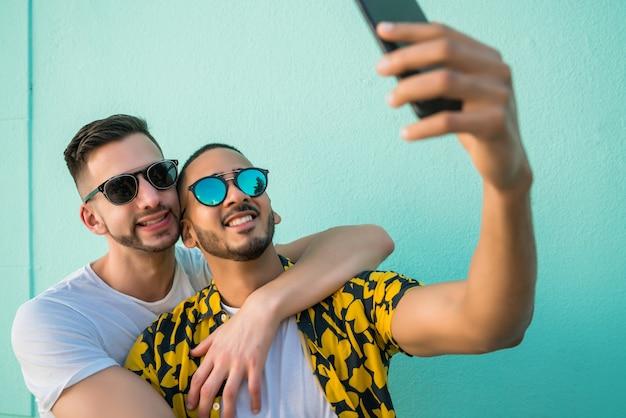 Pareja gay tomando un selfie con teléfono móvil.